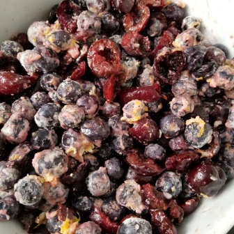 The blueberries and cherries mixed with flour, sugar, and lemon zest.